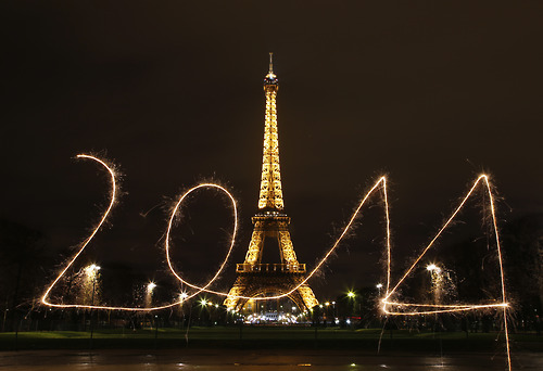 "A reveller writes ""2014"" with sparklers ahead of New Year's Eve, in front of the Eiffel Tower in Paris"